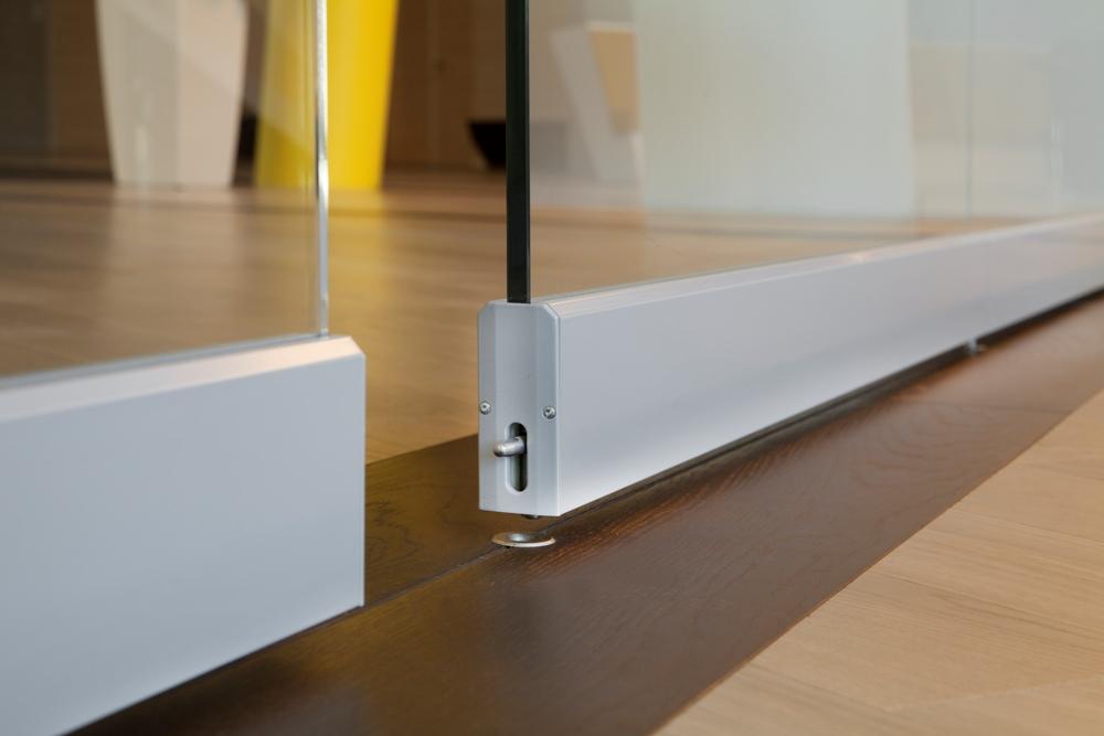 Aura 920 lasisiirtoseinä, lattiasalpa lukitsee elementit seinälinjalle. Profiilit polttomaalattu sävyyn RAL 7035